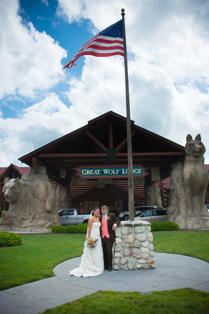 Great Wolf lodge wedding posing in front of the lodge in Williamsburg