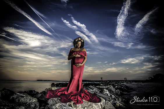 Maternity Photography in Virginia Beach of a mother to be on the rocks in a red dress during a maternity session.