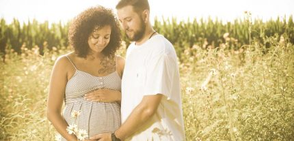 Maternity photographer in Virginia with a couple on the edge of a flower field.
