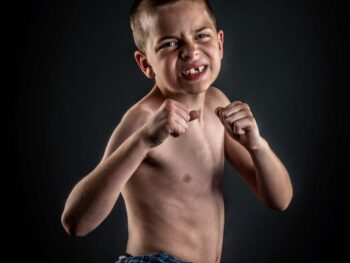 Young man who lost a tooth posing as a fighter in studio in Virginia Beach for his missing tooth photography session